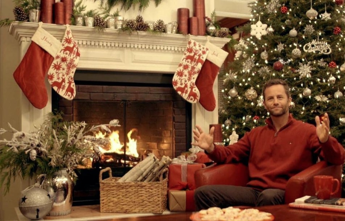 kirk cameron in front of fireplace in christmas clothing in saving christmas