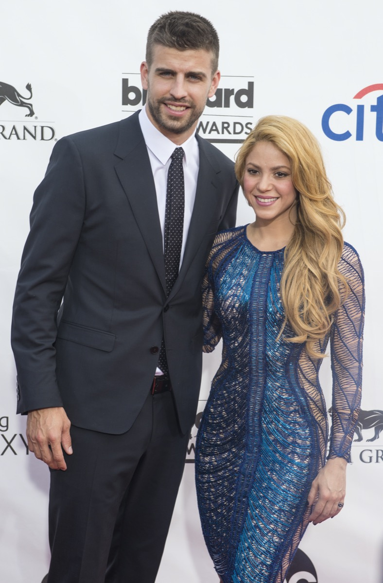 Gerard Pique wears a black suit and Shakira wears a blue dress at the Billboard Music Awards in 2014
