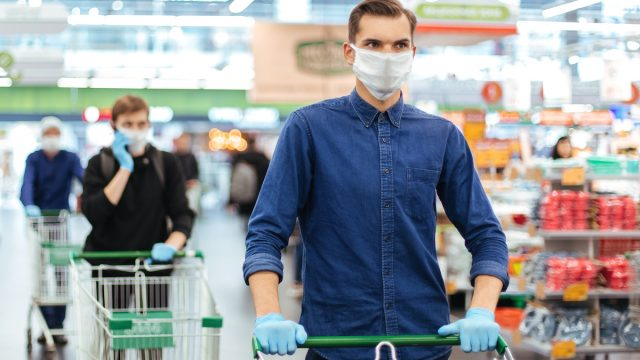 oung man in a protective mask with a shopping cart at store