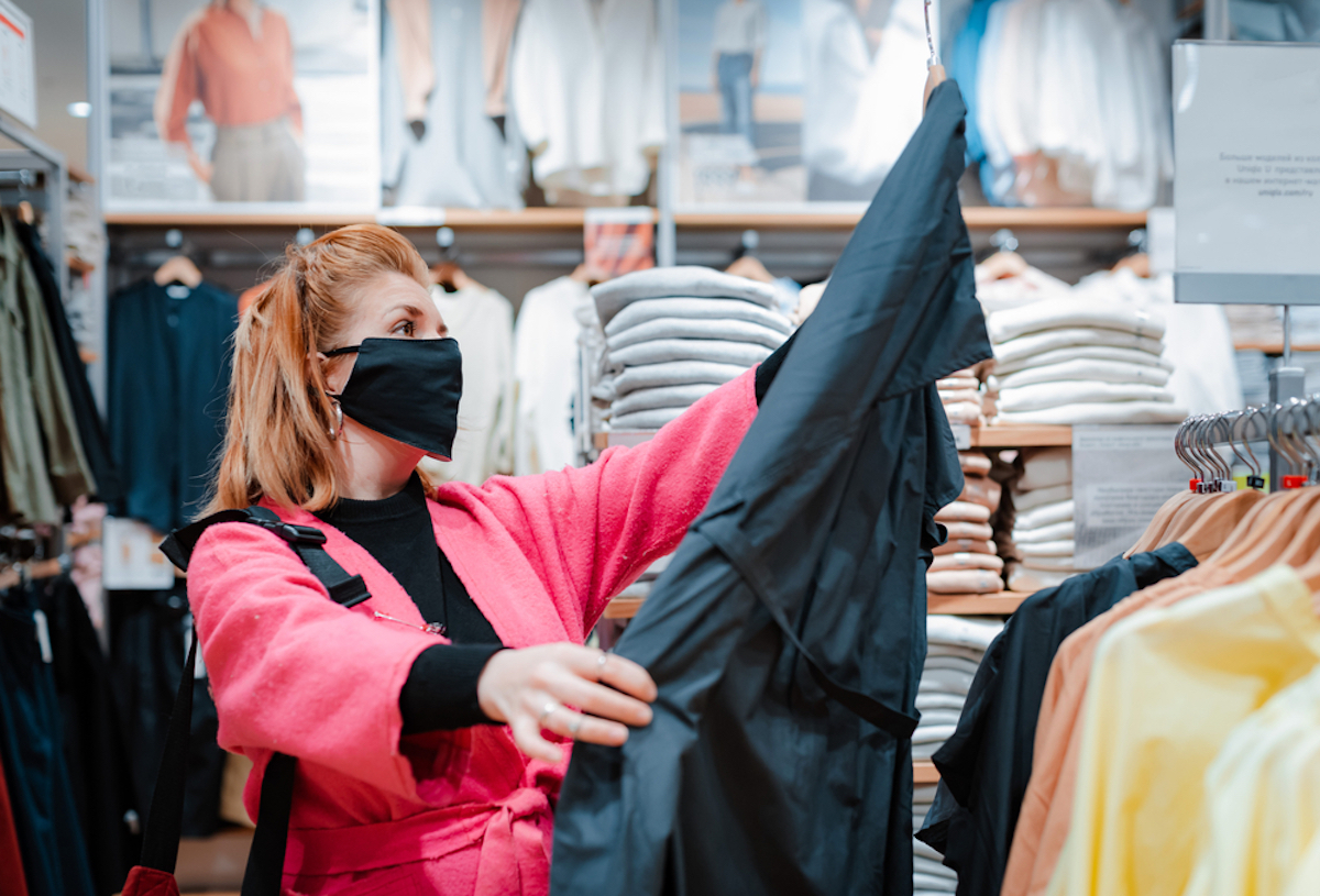 white woman with brown hair wearing face mask and bright pink coat while shopping at mall and looking at a jacket