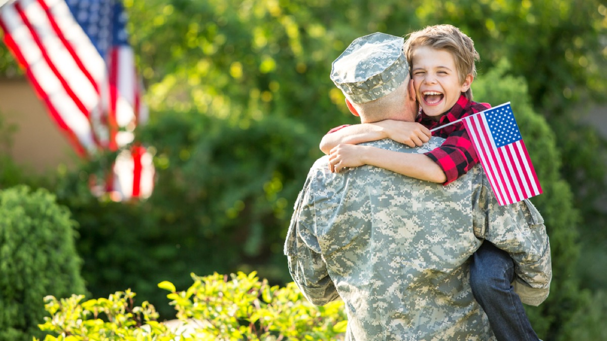white man in military uniform hugging young son