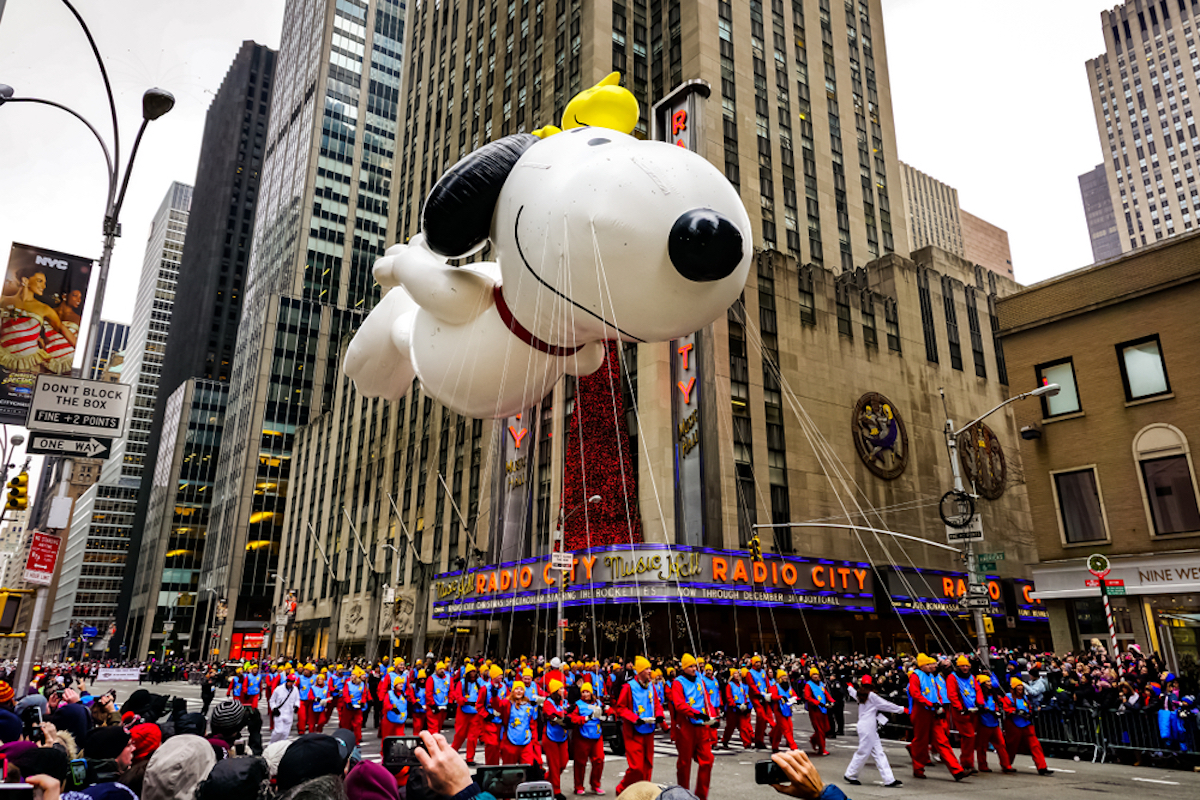 Snoopy balloon floats in the air during the annual Macy's Thanksgiving Day parade along Avenue of Americas with the Radio Music Hall in the background on November 27, 2014.