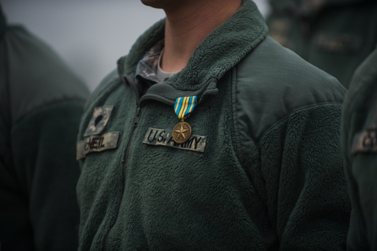 """the chest of a military man wearing a green """"U.S. Army"""" jacket with an award pinned to it"""