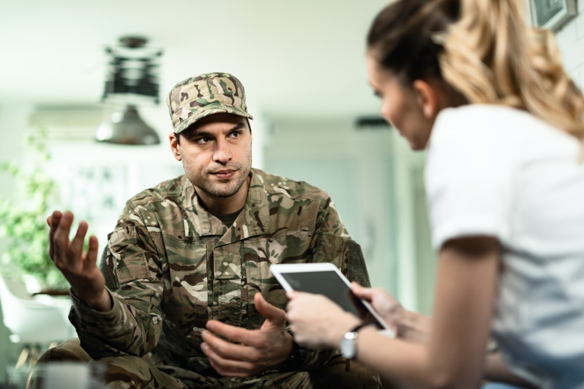 veteran with his arms open and talking to a female doctor who is holding a tablet