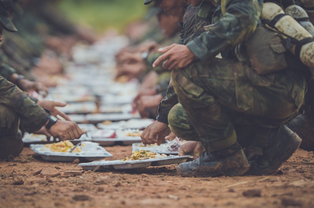 soldier arms reached out and legs bent down as they eat food