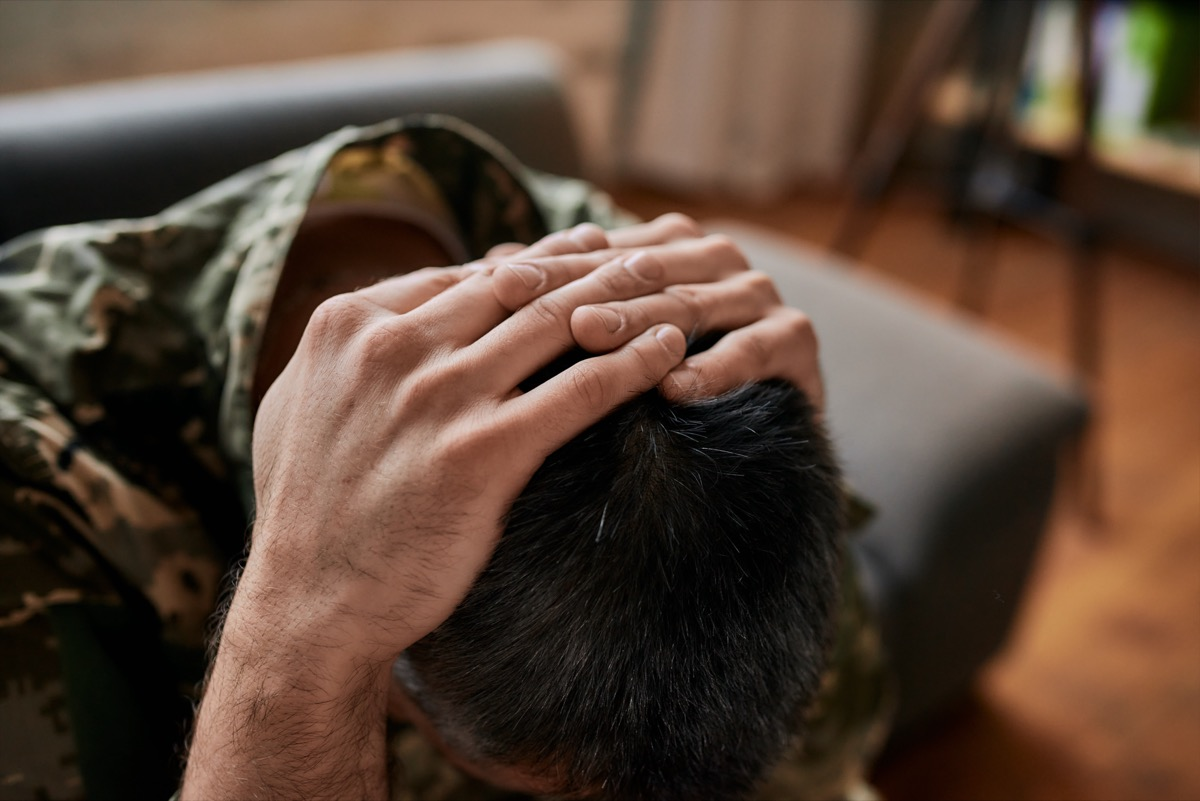 military man sitting down with his head in his hands