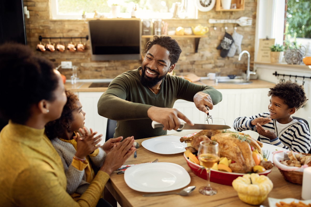 Smiling black man having Thanksgiving lunch with his family and carving stuffed turkey at dining table, surrounded by wife and children