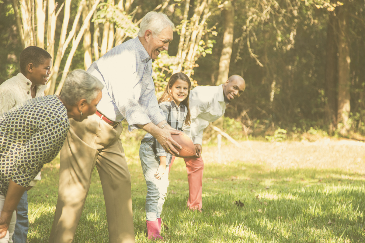 Multi-ethnic, multi-generation family members playing a football game together in grandparents' backyard on Thanksgiving Day