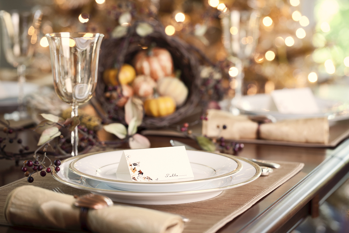 Autumn holiday Thanksgiving dining with place cards and traditional centerpiece filled with pumpkins and gourds.