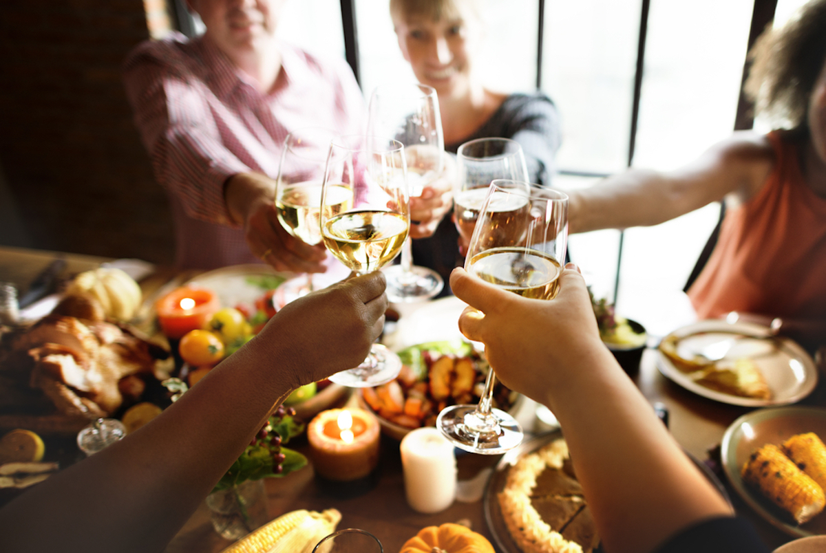 closeup of hands clanking wine glasses over thanksgiving table