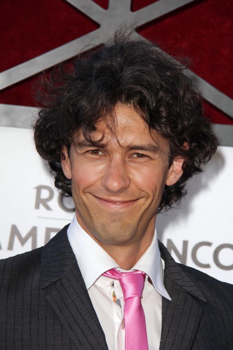 Tom Franco wears black jacket and pink tie in 2013