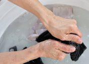 Woman's hands washing a bra in basin