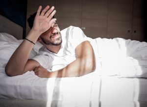 A man wakes up in bed under stress