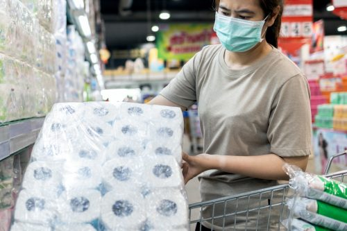 woman buying toilet paper while wearing a mask