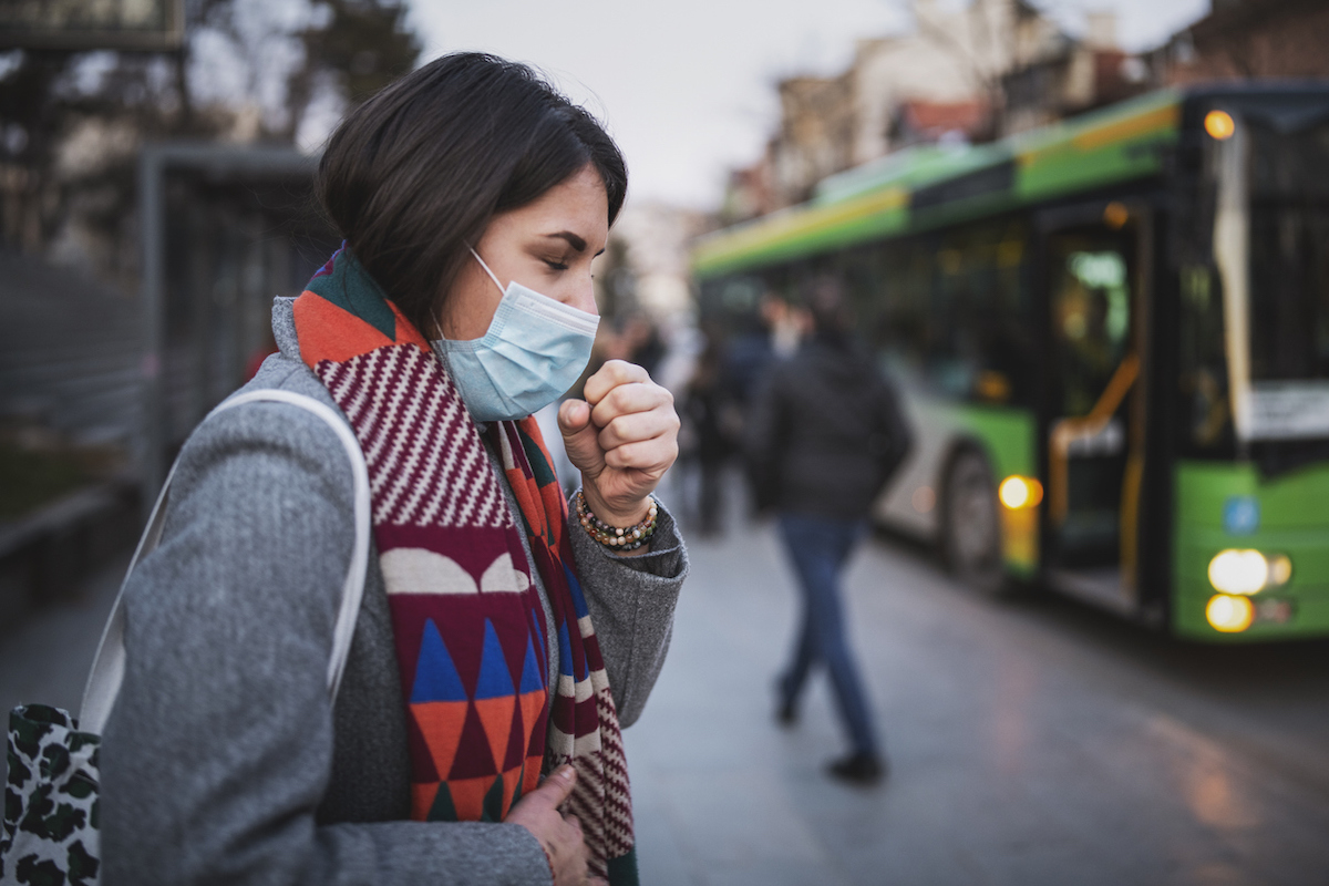 Side view of woman wearing a face mask and coughing while standing at bus stop