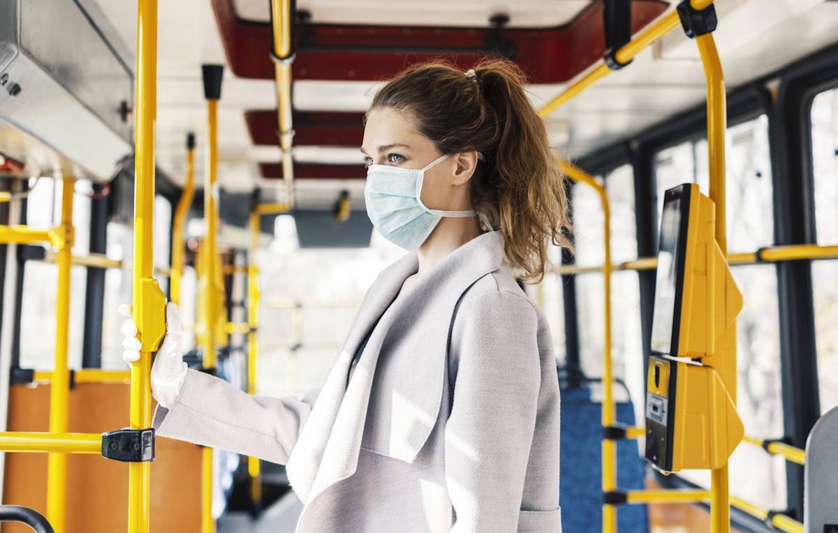 Woman wearing surgical protective mask going to work, holding railing of bus