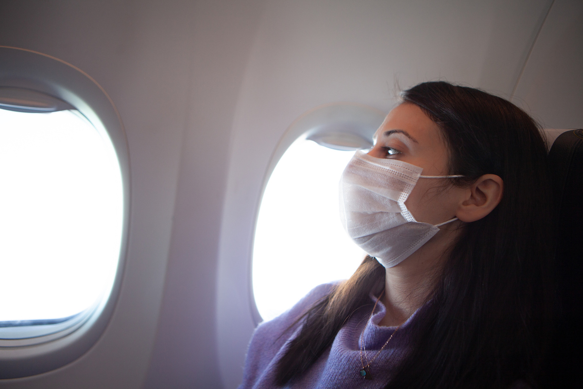 Woman with protective mask in a plane