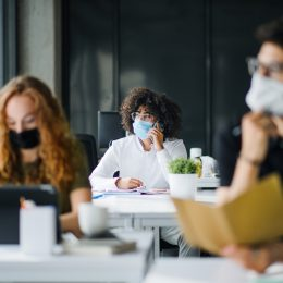 A young woman wearing a face mask sits in an office with coworkers also wearing face masks.
