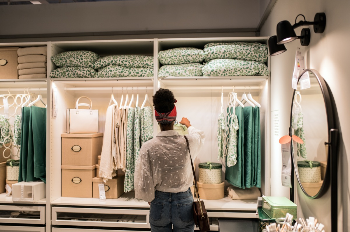 African-American woman from behind as she looks at colorful and organized displays at a furniture store