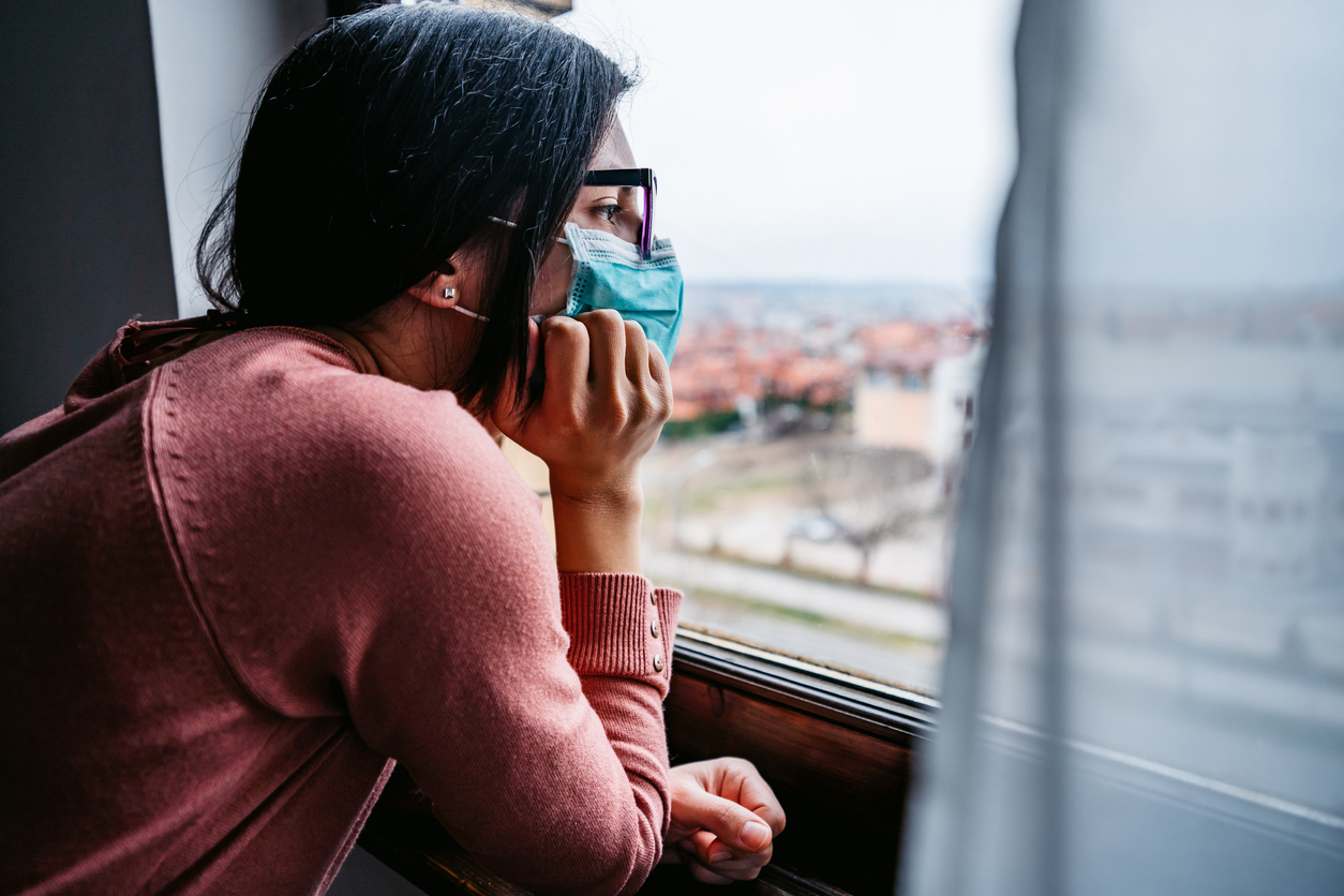 A young woman wearing glasses and a face mask looks out her window during a COVID lockdown