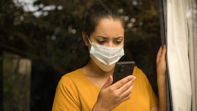 young woman wearing a face mask looking at her smartphone