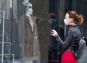 young white woman wearing mask looking into shop window