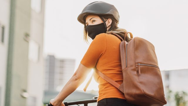 Young adult riding a bicycle through the city wearing face mask against COVID-19