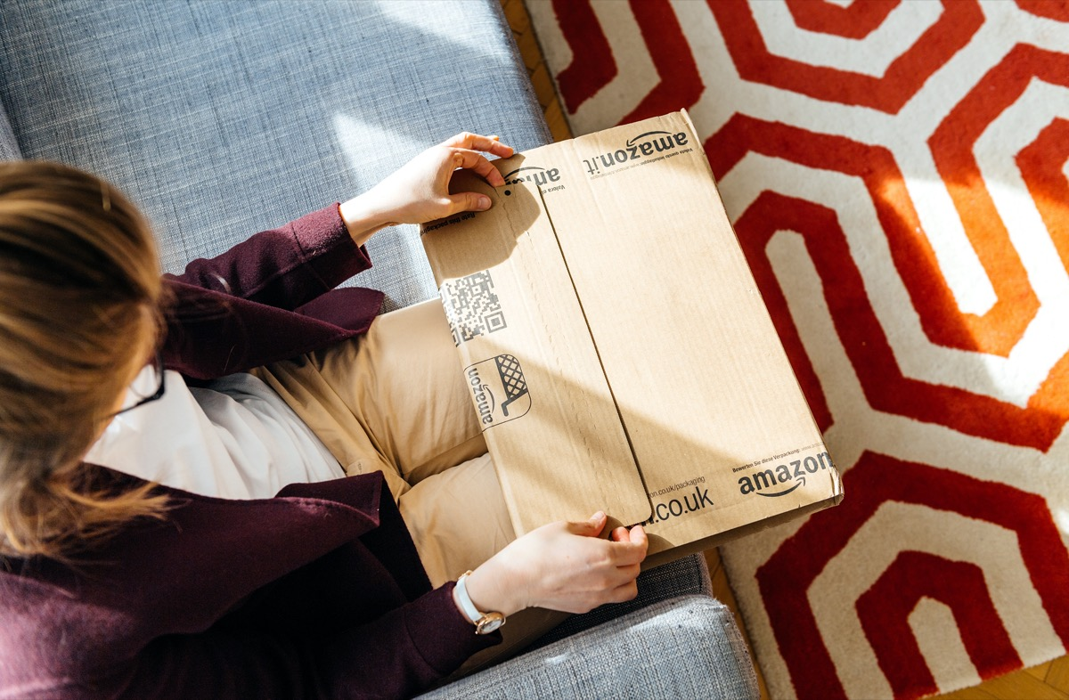 PARIS, FRANCE - APR 24 2017: Living room view from above of woman unpacking unboxing Amazon cardboard box logotype printed cardboard box side. Amazon Inc is the an American e-commerce shopping company