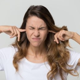 woman in a white shirt plugging her fingers in her ears
