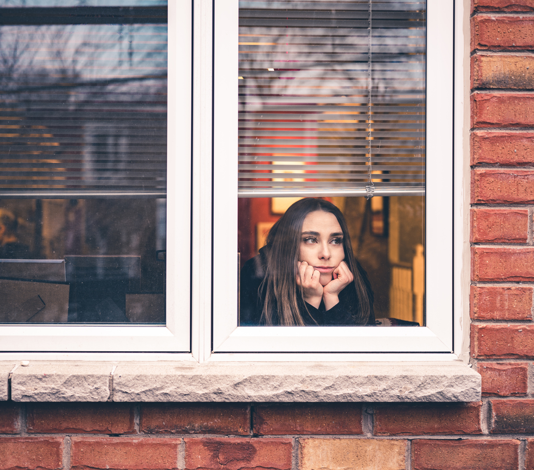 A young woman looks out her window with a distressed look on her face due to coronavirus lockdowns