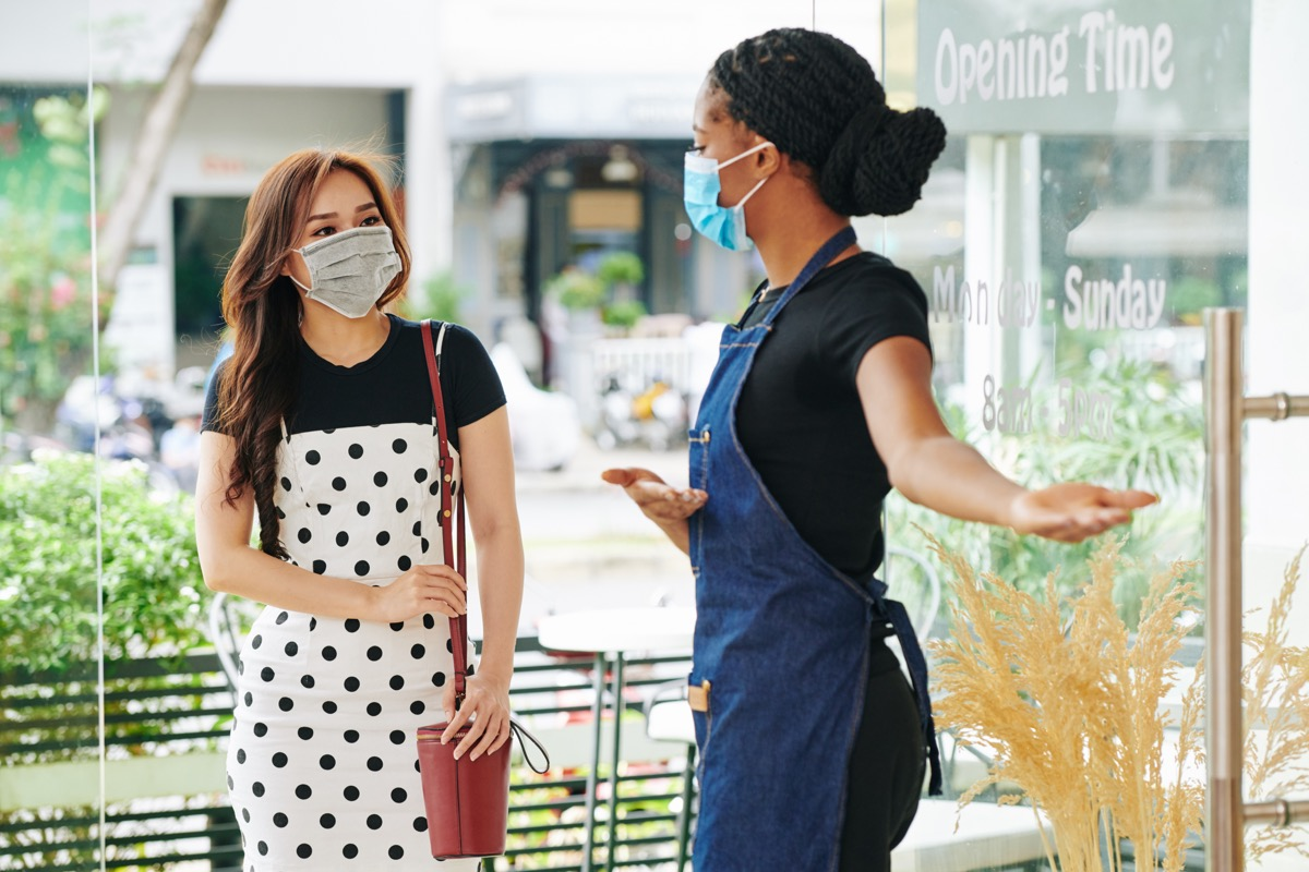 Waitress in apron and medical mask making welcoming gesture when inviting pretty young woman