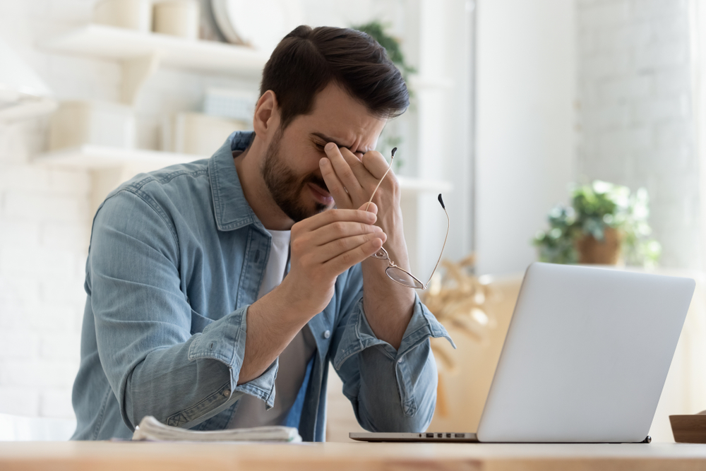 A young man working at a laptop takes off his glasses to rub his eyes with a sleepy, fatigued look