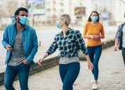 A group of young people walking down the street while wearing face masks.
