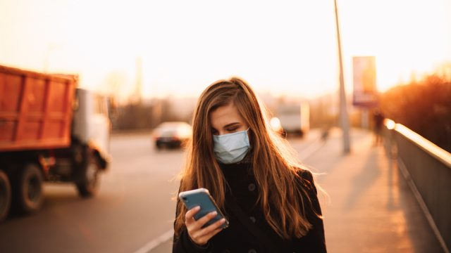 young woman wearing protective face medical mask using smart phone while walking on empty sidewalk on bridge in city at sunset