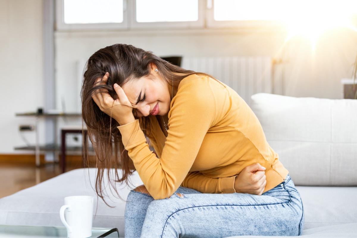 young woman hunched over with stomach pain