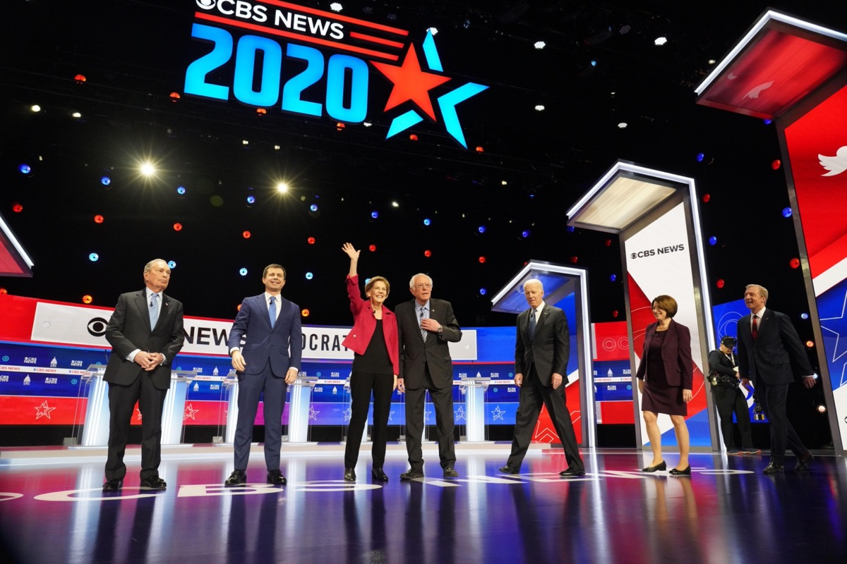 seven Democratic Candidates for U.S. President walking on stage for the debate in February 2020