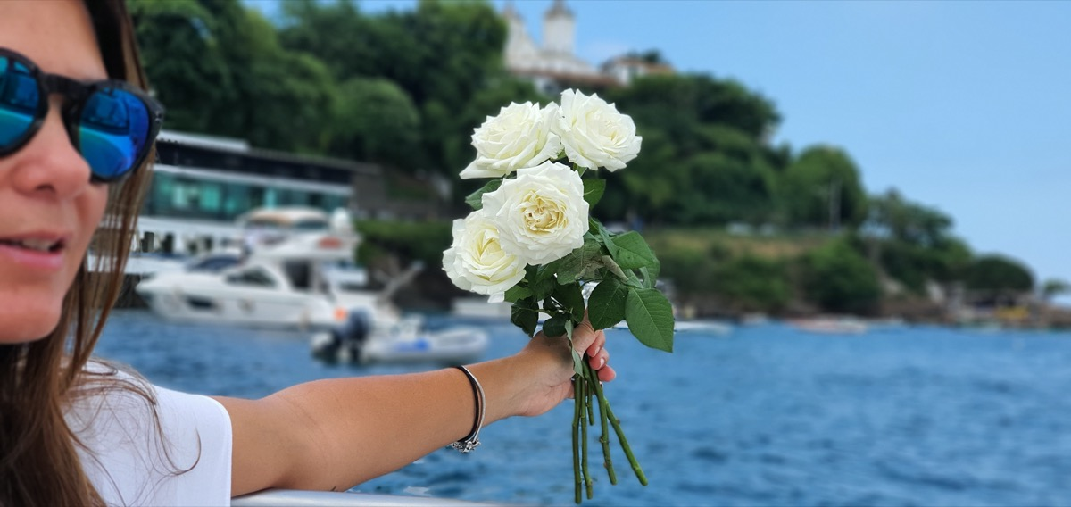 Young woman dropping white flowers into ocean