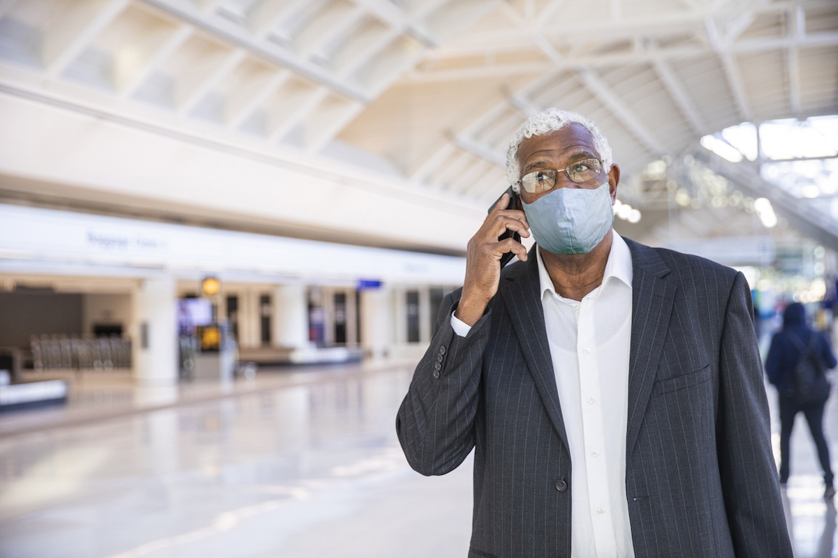 A Senior man using his phone in the airport while wearing a face mask during COVID