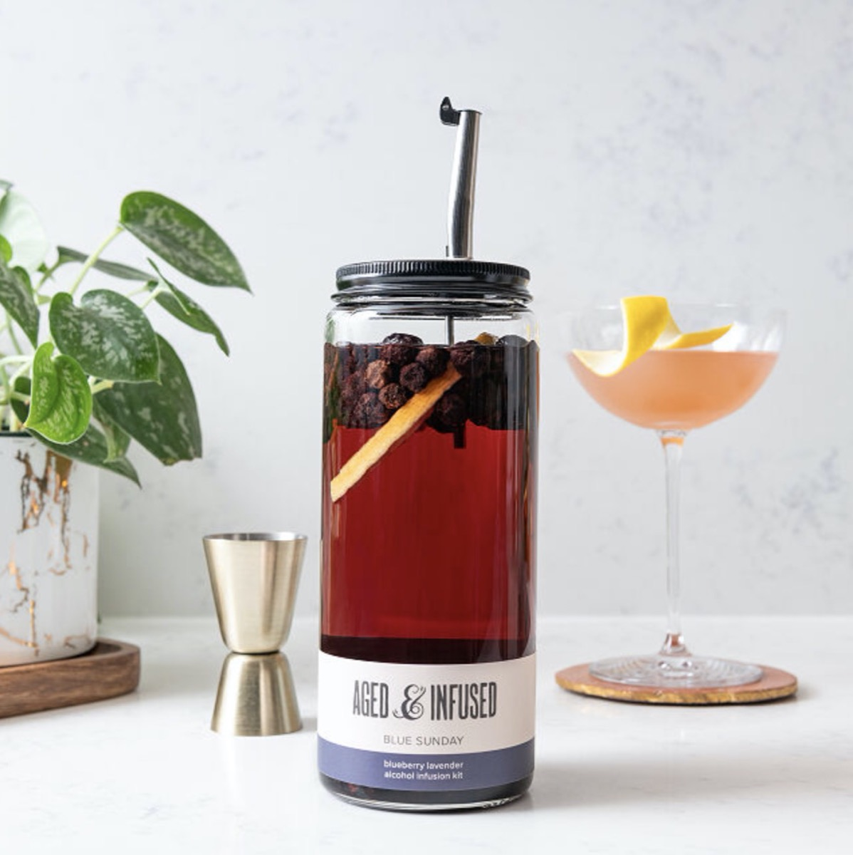 bottle with mason jar lid and silver straw next to jigger and glass with pink cocktail in it and a plant to the left