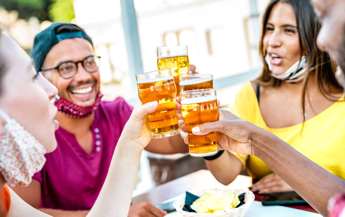 Friends toasting beer glasses with face masks pulled down