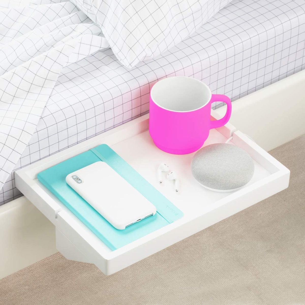 white shelf with coffee and phone next to bed