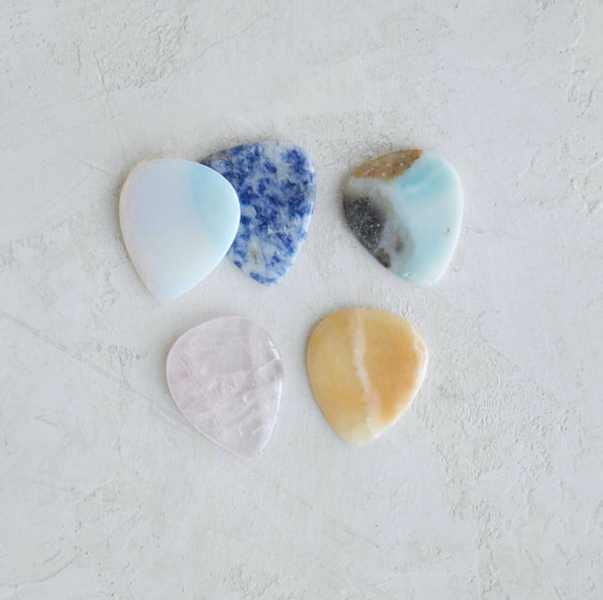 guitar picks made out of birthstones on white background