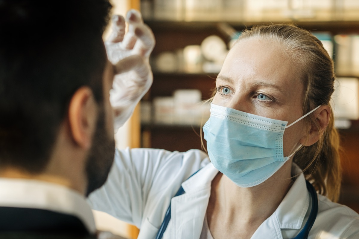 Female healthcare worker wearing surgical mask examining male patient. Doctor checking eyes of mid adult man. They are at a hospital.