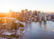 An aerial photo of the skyline of Boston, Massachusetts, taken at sunset from the water.