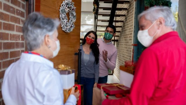 Happy senior couple arriving home for Christmas wearing facemasks and carrying presents while greeting to their kids - COVID-19 pandemic lifestyle concepts