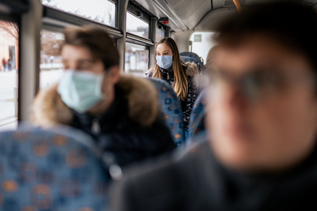 Woman wearing face mask on bus because of the new Coronavirus