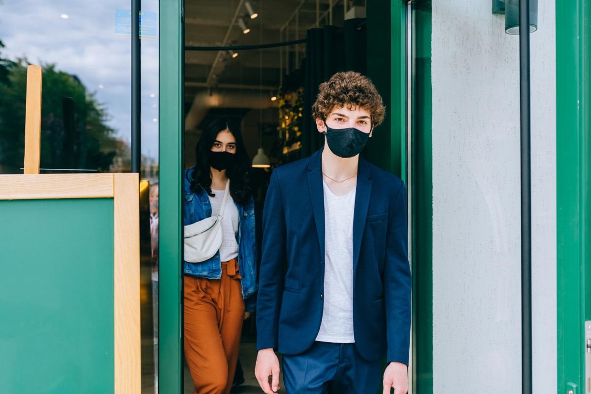 People in masks leaving a cafe together
