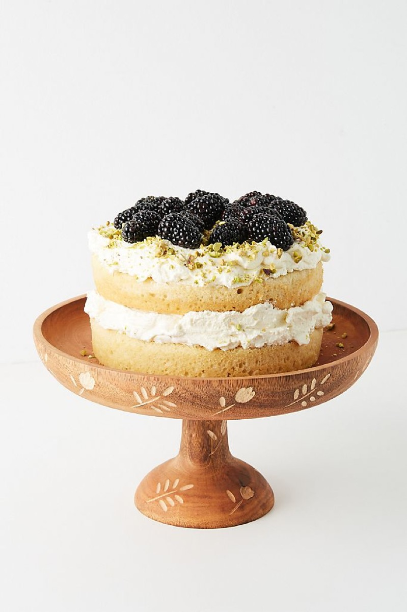 wooden cake stand with inlaid designs and cake with blackberries on it