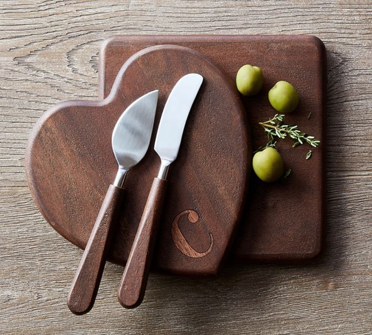 square and heart-shaped wooden cutting boards with cheese knives on top