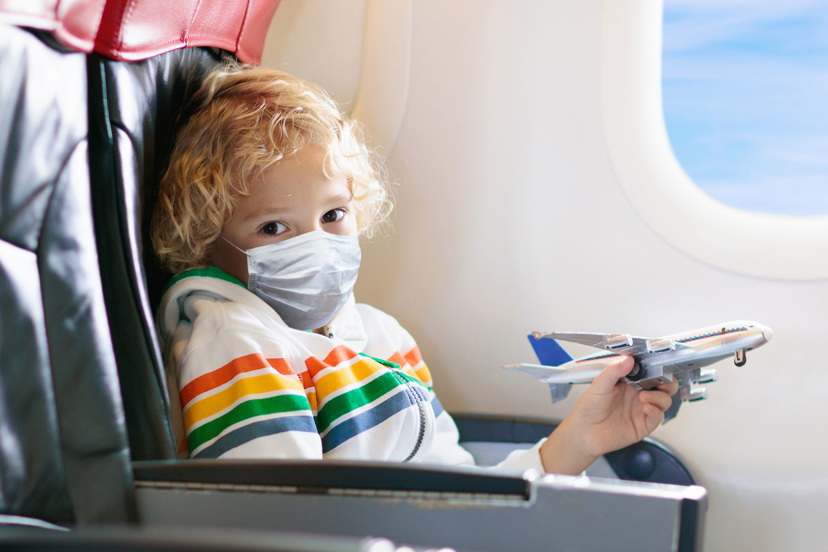 Child in airplane in face mask